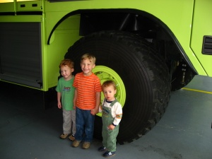 Three little boys by a large firetruck wheel